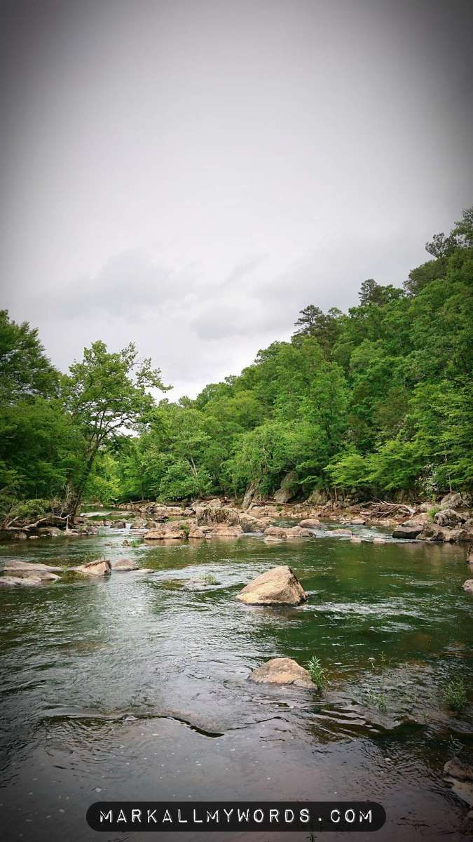 Eno River with boulders and green forest