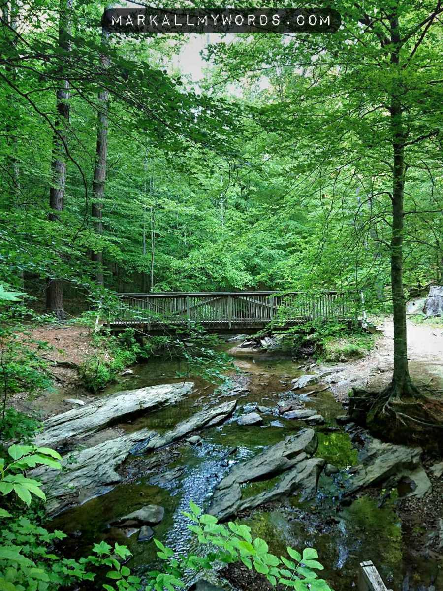 Creek with big stones and wooden footbridge