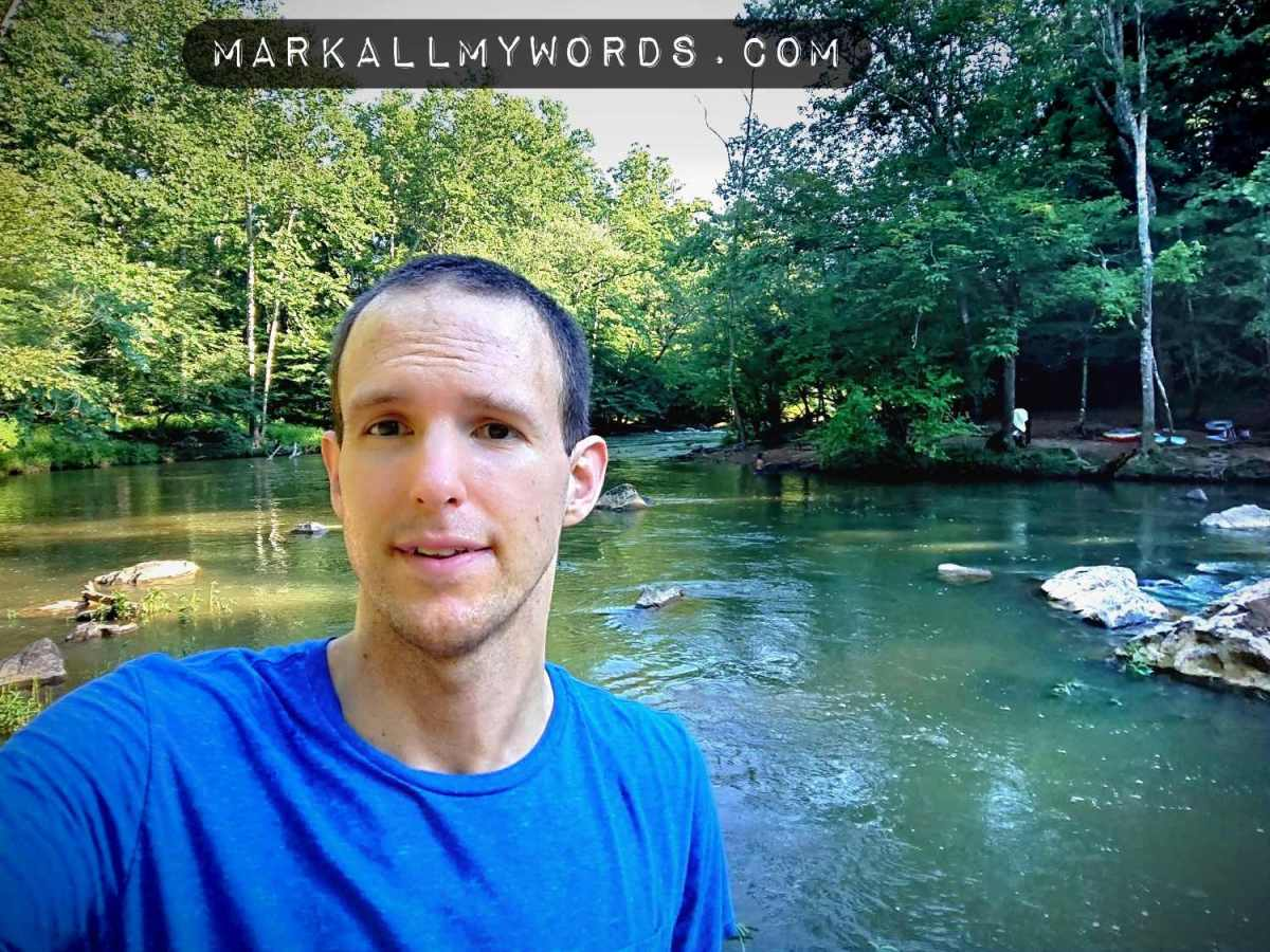 White guy, author Mark Miles, with blue shirt next to river