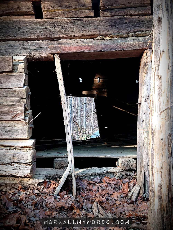 Dilapidated doorway to old wooden cabin