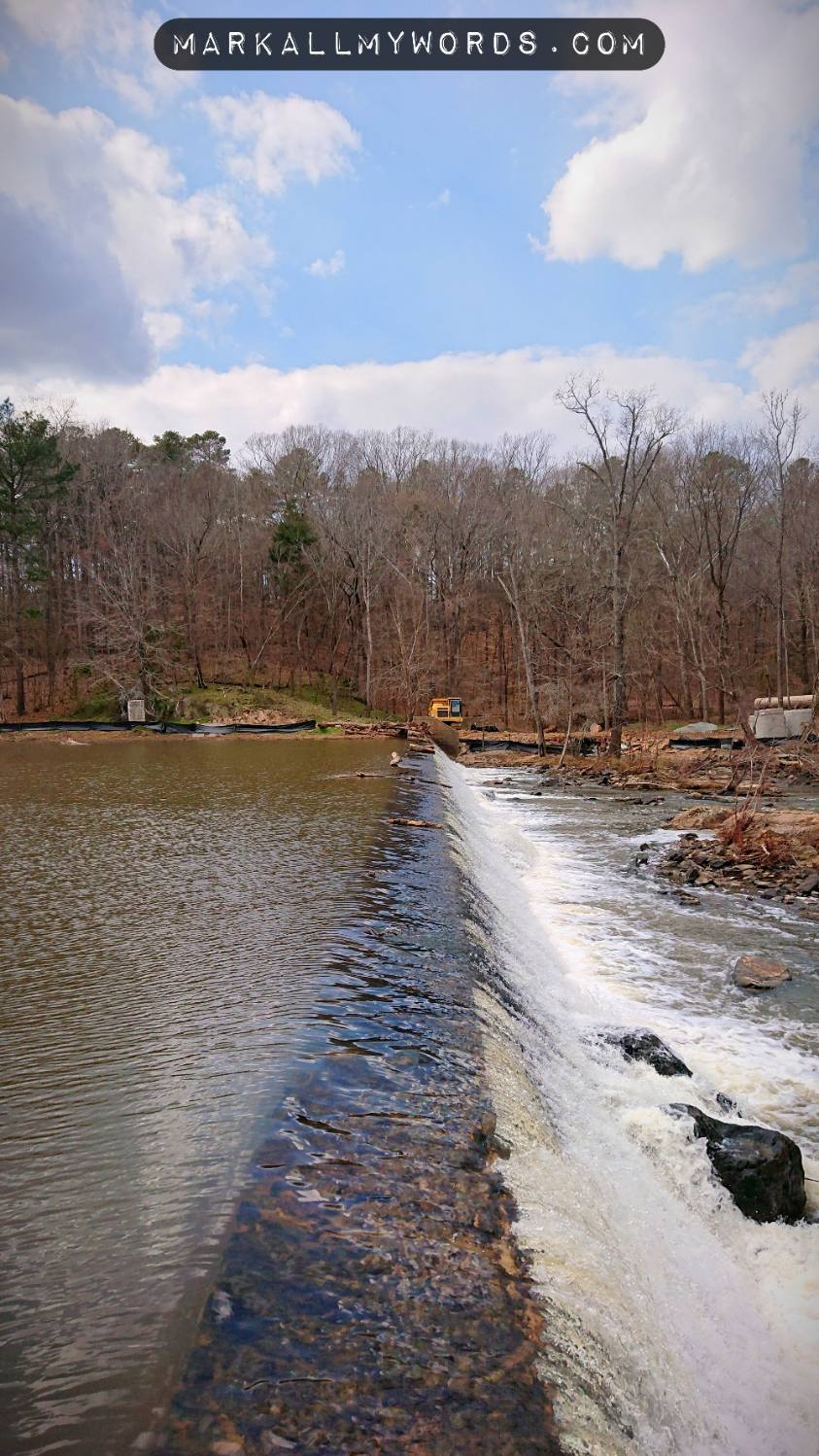Mill dam with construction equipment in distance