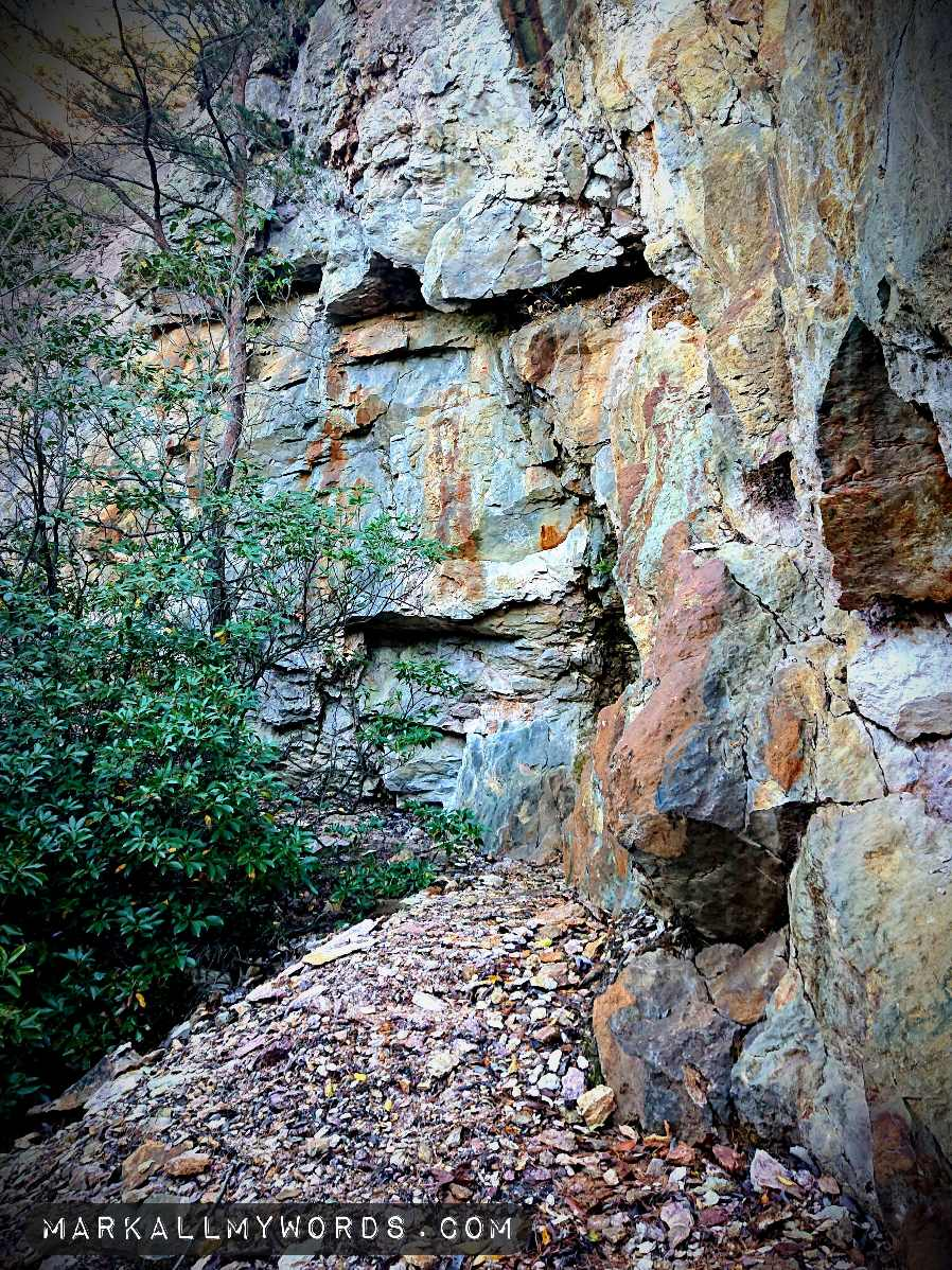 Blue-green and orange rock wall at quarry