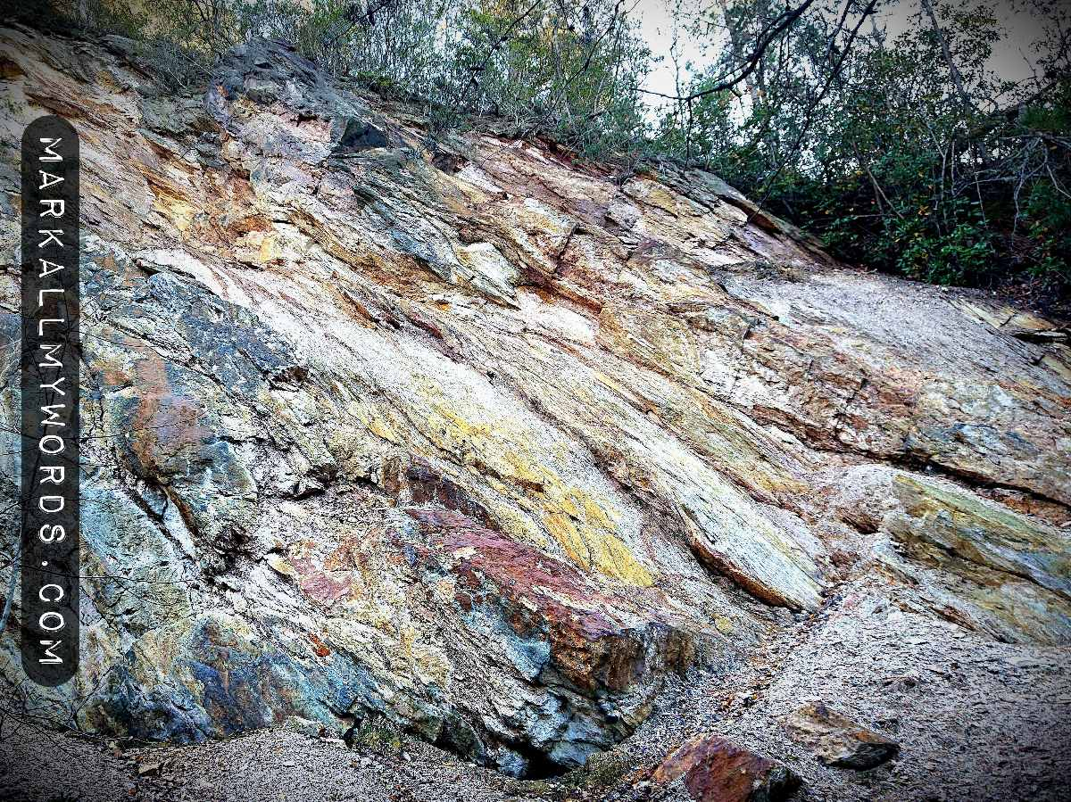 White, yellow, red, and blue-green strata of rock